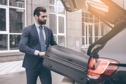 Young business person travel by vehicle put baggage